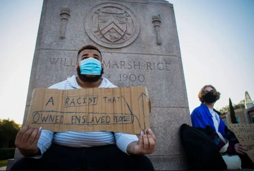 Shifa Rahman holds a protest sign at the base of the William Marsh Rice statue on the Rice University campus.