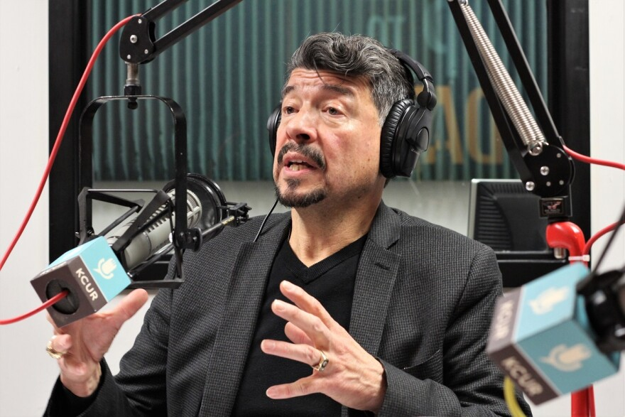 A man with dark hair and a goatee wearing headphones and a charcoal jacket sits behind a microphone in a radio studio.