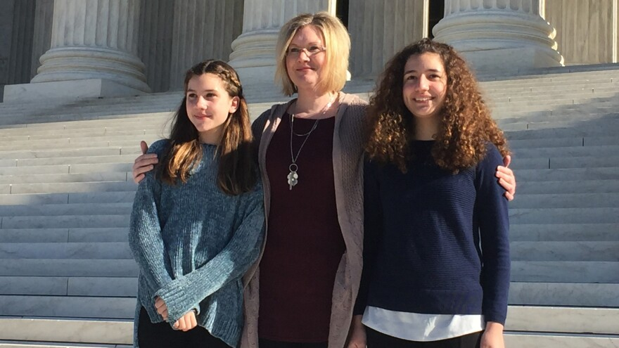 Kendra Espinoza stands with her daughters outside the U.S. Supreme Court on Wednesday. Espinoza is the lead plaintiff in a case that could make it easier to use public money to pay for religious schooling.