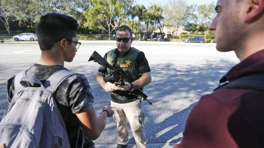A law enforcement officer equipped with a rifle talks with students at Marjory Stoneman Douglas High School after a shooter killed 17 people on the campus on Feb. 14, 2018.