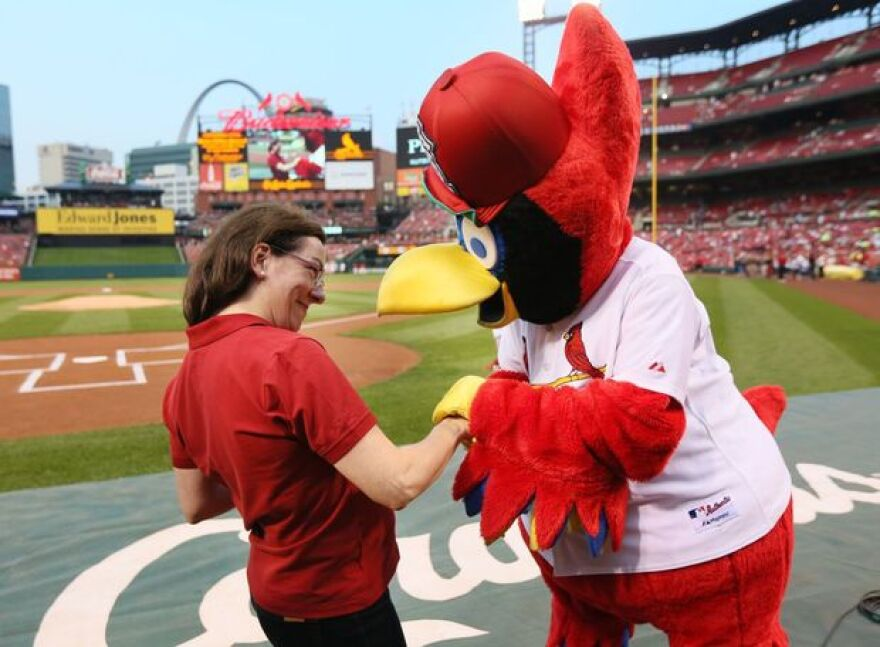 Marie-Hélène Bernard laughs with Fred Bird at an August Cardinals game in which she threw out the first pitch.