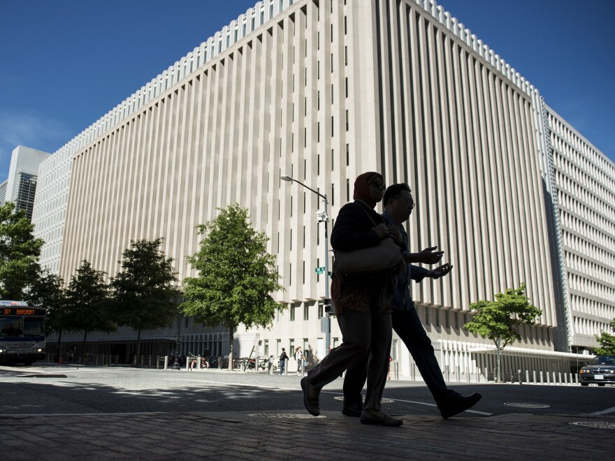 People walk past the World Bank's headquarters in Washington, D.C. A watchdog says that the World Bank is not adequately monitoring how funds intended for Afghanistan reconstruction are being used.