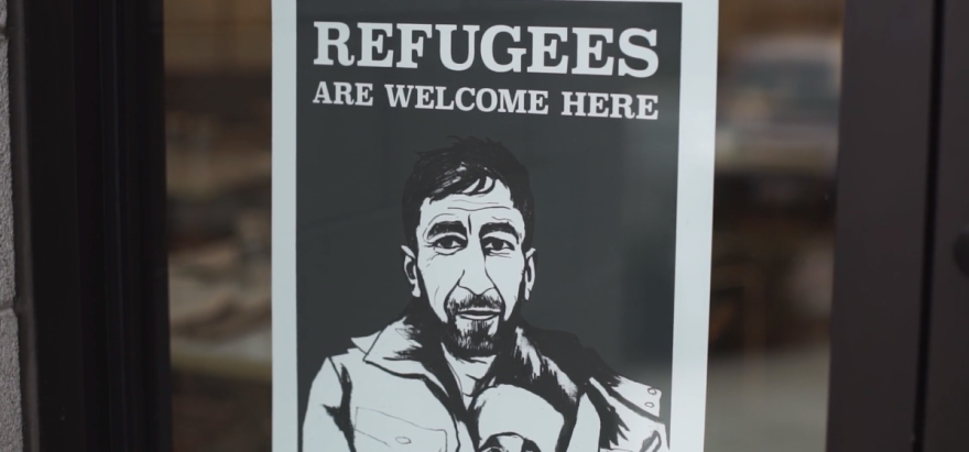 A photo of a poster, displayed in a restaurant window and featuring a bearded man, reads refugees are welcome here.