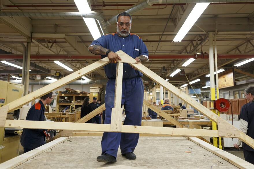 Pedro Rivera, 51, carries a wooden structure after helping disassemble part of a roof during the woodworking and carpentry portion of a Vocational Village program at a correctional facility in Ionia, Mich. The skilled trades training program also includes education for plumbing, carpentry and more.