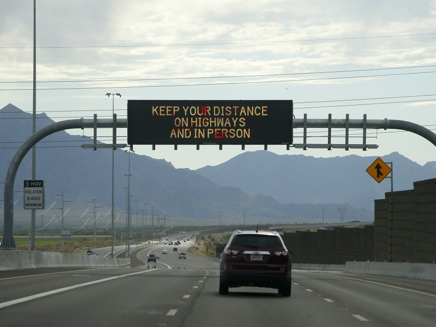A public service announcement on a traffic sign from the Arizona Department of Transportation reminds motorists of the coronavirus outbreak on July 19 in Phoenix.