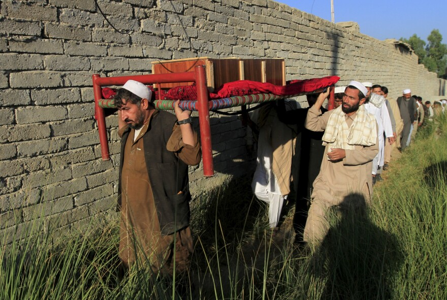 Afghan men carry a coffin of an earthquake victim for burial in the Behsud district of Nangarhar province, Afghanistan, on Tuesday.