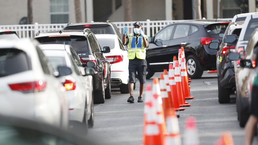 A public safety officer directs drivers where to go last week at a coronavirus testing site at the Lee Davis Community Resource Center in Tampa, Fla.