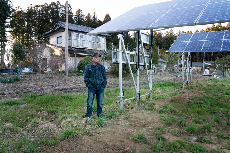Shigeyuki Konno, 74, stands outside his home where he rents his land out for a power company to install solar panels.