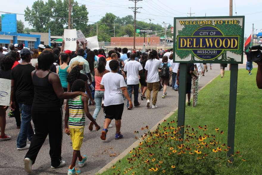 Demonstrators walk past the Dellwood city line on their way to Greater St. Mark Family Church on Sunday.