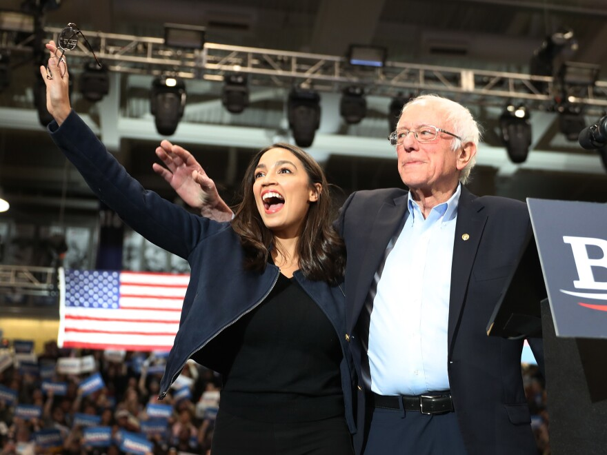 Rep. Alexandria Ocasio-Cortez and Sen. Bernie Sanders stand together during a February campaign event at the Whittemore Center Arena in Durham, N.H.