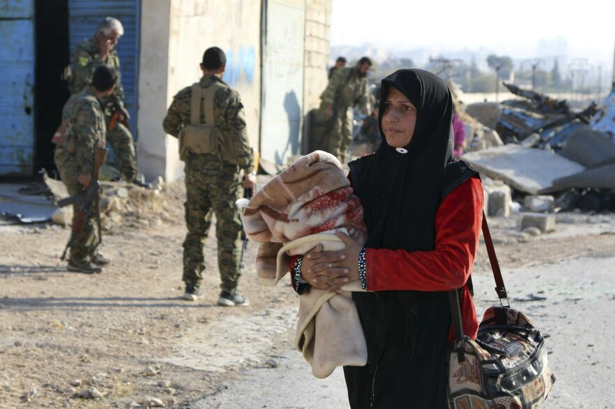A Syrian woman carries her belongings past Kurdish fighters as she flees on Sunday. The Syrian Observatory for Human Rights says shelling has killed 26 people who were trying to flee eastern Aleppo.