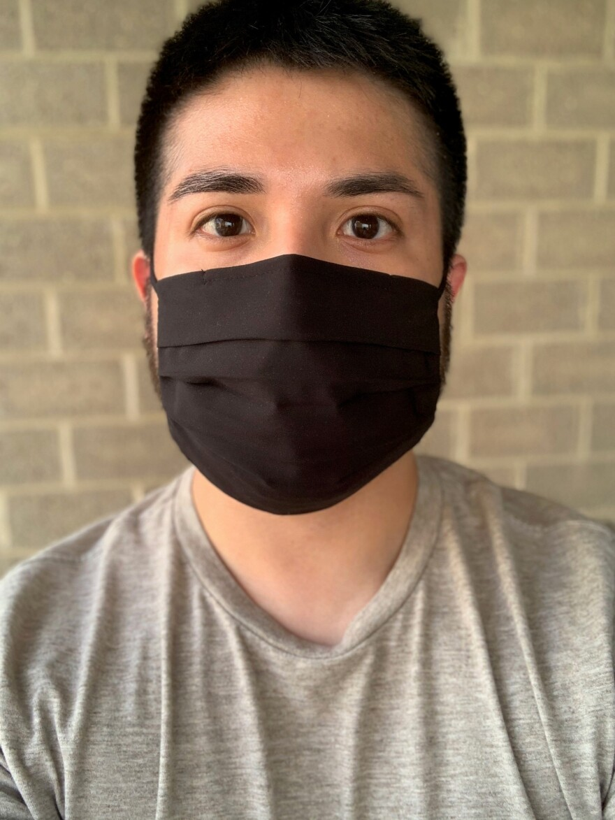 A man poses in a black face mask and gray shirt.