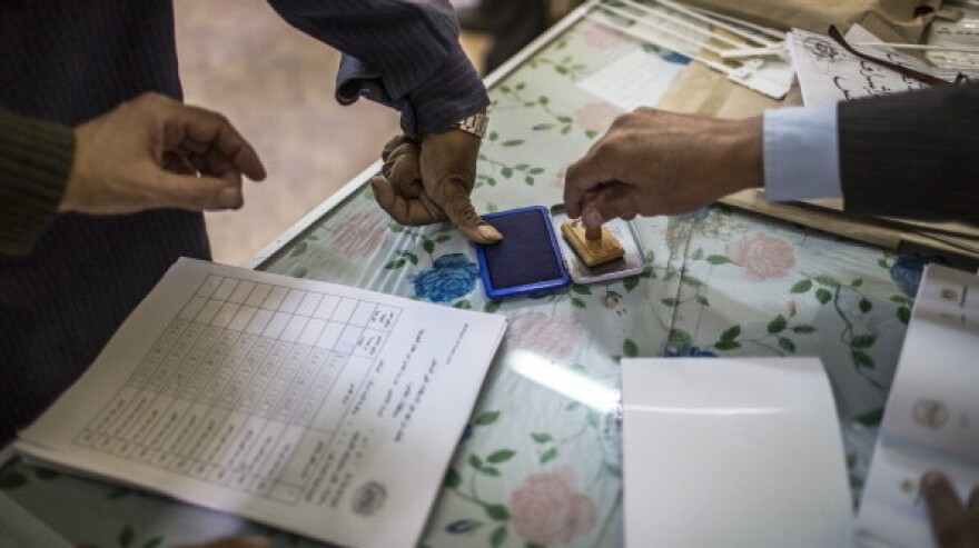 In Cairo earlier today, a man dips his finger on an ink pad so that he can mark having voted during a referendum on the new Egyptian constitution.
