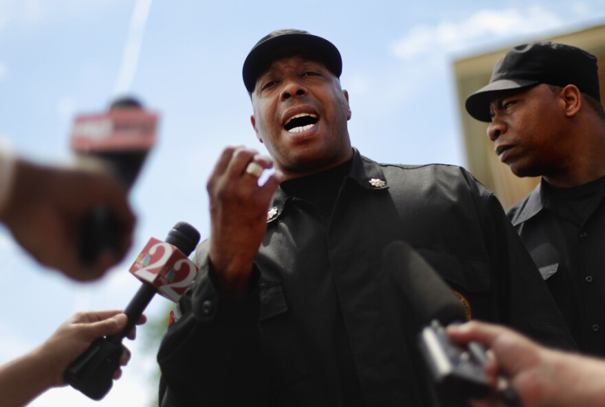Mikhail Muhammad of the New Black Panther Party speaks to the media next to a memorial to Trayvon Martin outside The Retreat at Twin Lakes community where Trayvon was shot and killed by George Michael Zimmerman.