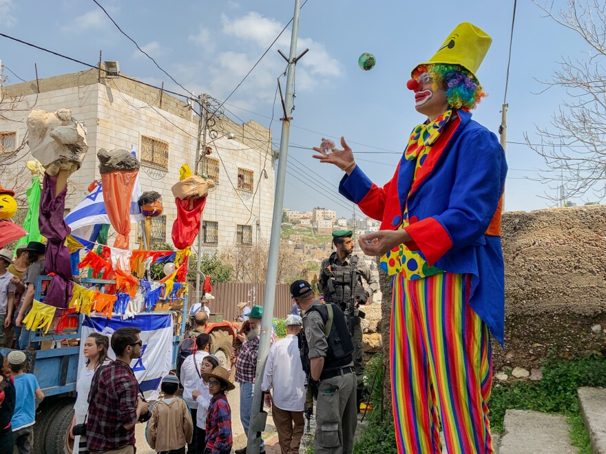 Israeli settlers celebrate Purim on al-Shuhada Street in the divided West Bank town of Hebron.
