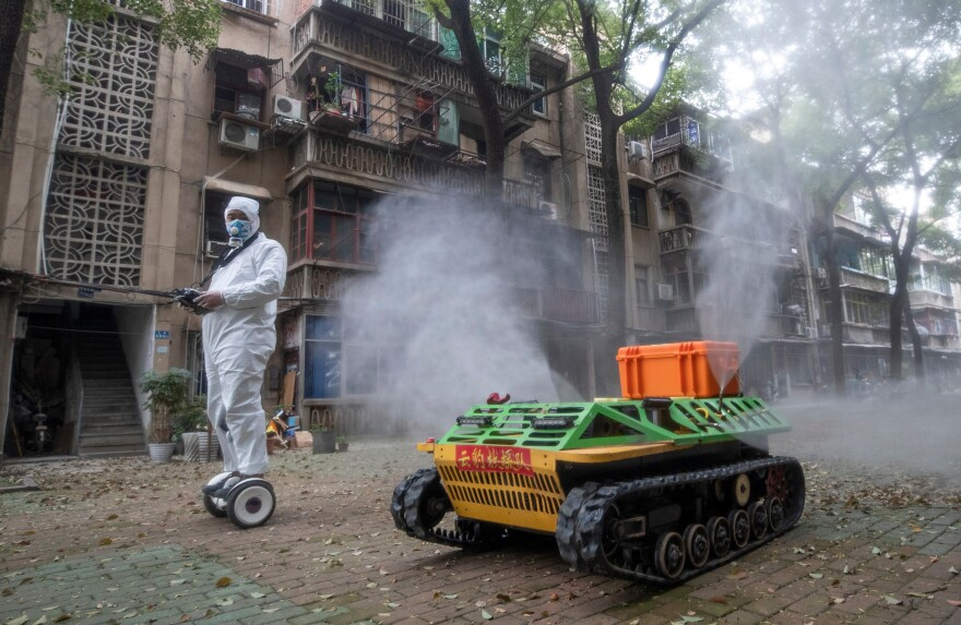 A volunteer operates a remote-controlled robot to disinfect a residential area in Wuhan, China, on March 16. The novel coronavirus was first identified in Wuhan in December.