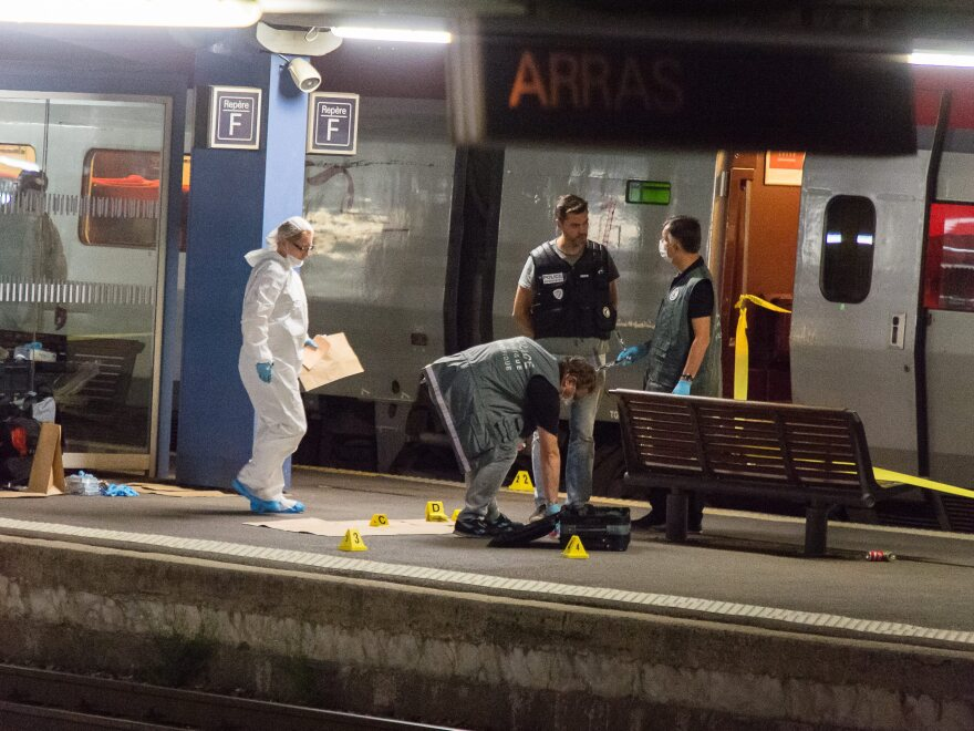Police work outside a train north of Paris where three people were wounded in an attack by a Kalashnikov-wielding gunman. The suspect was reportedly subdued by two U.S. Marines, one of whom was seriously wounded.