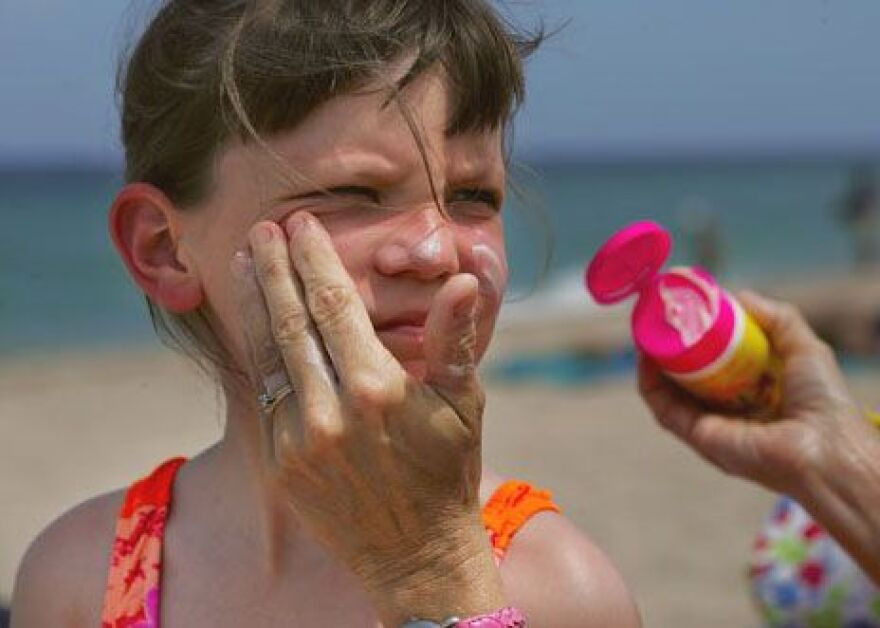 Sunscreen being applied to child's face.