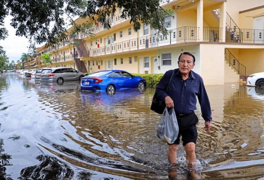 Man walks through flooded road
