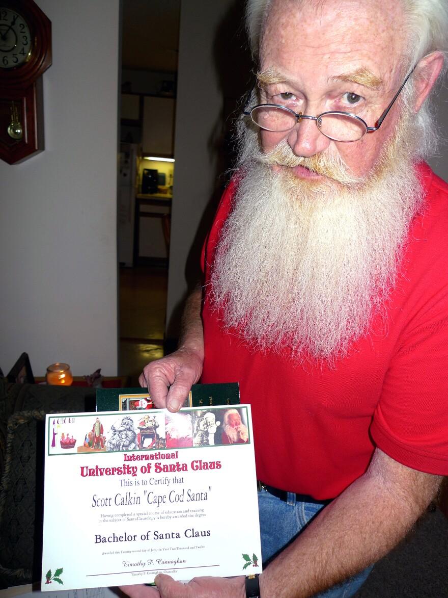 Scott Calkin, aka Cape Cod Santa, shows his diploma from the International University of Santa Claus.