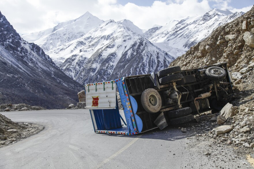 A cargo truck lies flipped on a hairpin turn on a far northern section of the Karakoram Highway near the border with China. The road is often narrow, clings to steep slopes and is battered by landslides and floods.