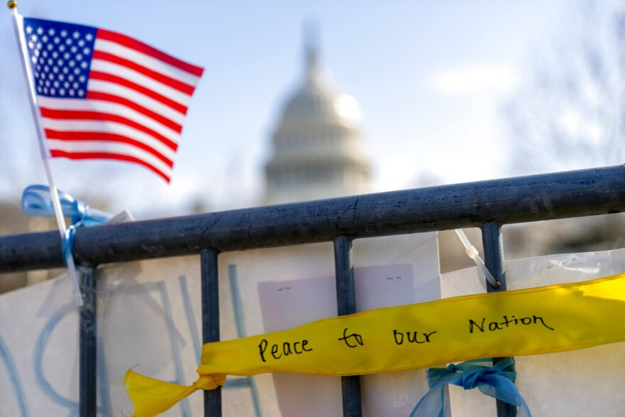 "A ribbon reading ""Peace to Our Nation"" is visible at a memorial for Capitol Police Officer Brian D. Sicknick near the Capitol Building on Capitol Hill in Washington, Thursday, Jan. 14, 2021. (AP Photo/Andrew Harnik)"