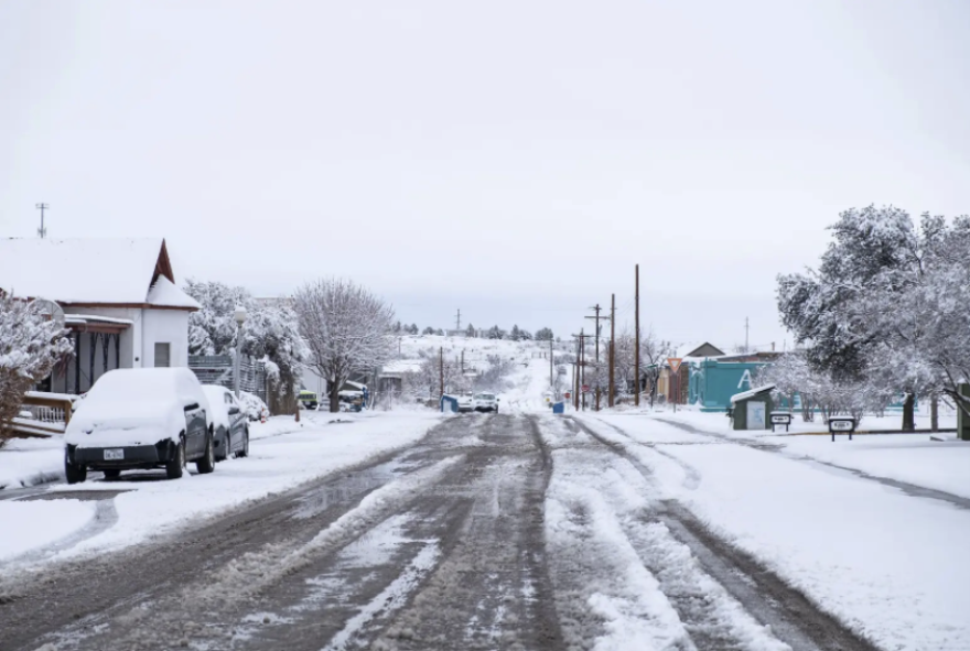 A snowy street in a rural neighborhood. Small houses line each side and the street is partially plowed. Snow blankets everything.