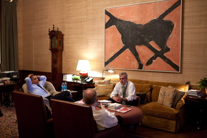 President Obama meets with national security aides John Brennan, foreground, and Denis McDonough in front of a painting titled <em>Butterfly</em> by Susan Rothenberg.