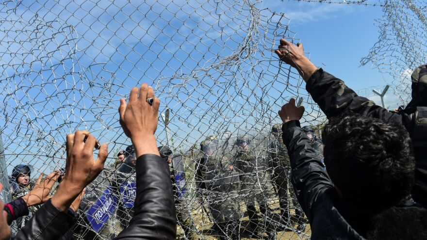 Migrants and refugees pull down a border fence during clashes with Macedonian forces Sunday near a makeshift migrant camp in the northern Greek border village of Idomeni.