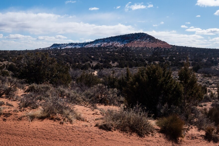 A snow-capped mound of red earth rises up on the horizon.