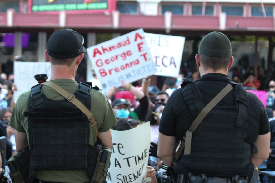 Two men look on at protestors in San Antonio on May 30.