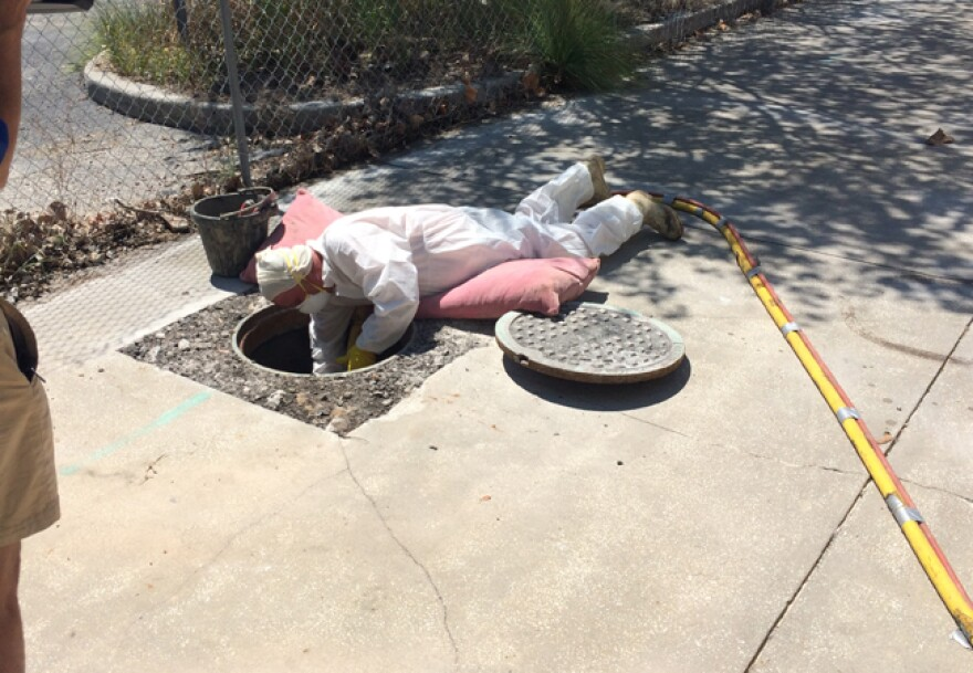 A worker reaches into a manhole while coating the concrete lining to prevent leaks.