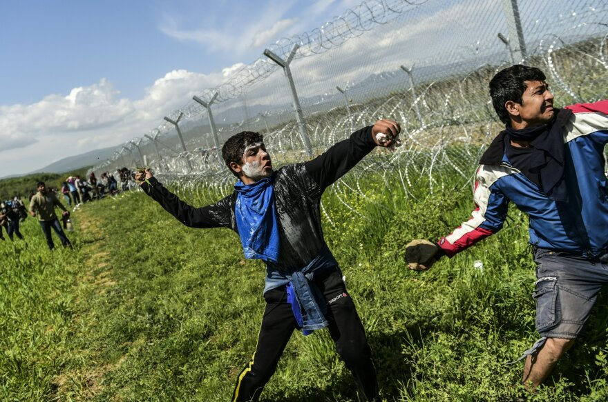 Refugees and migrants clash with Macedonian soldiers as they storm the border fence near Idomeni on Sunday.