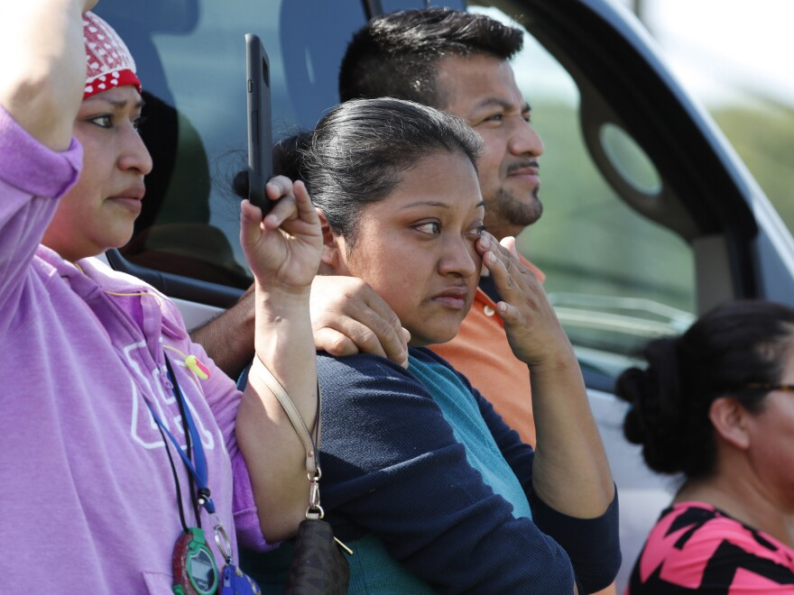 Friends, co-workers and family watch as U.S. immigration officials raid the Koch Foods Inc. plant in Morton, Miss., on Wednesday.
