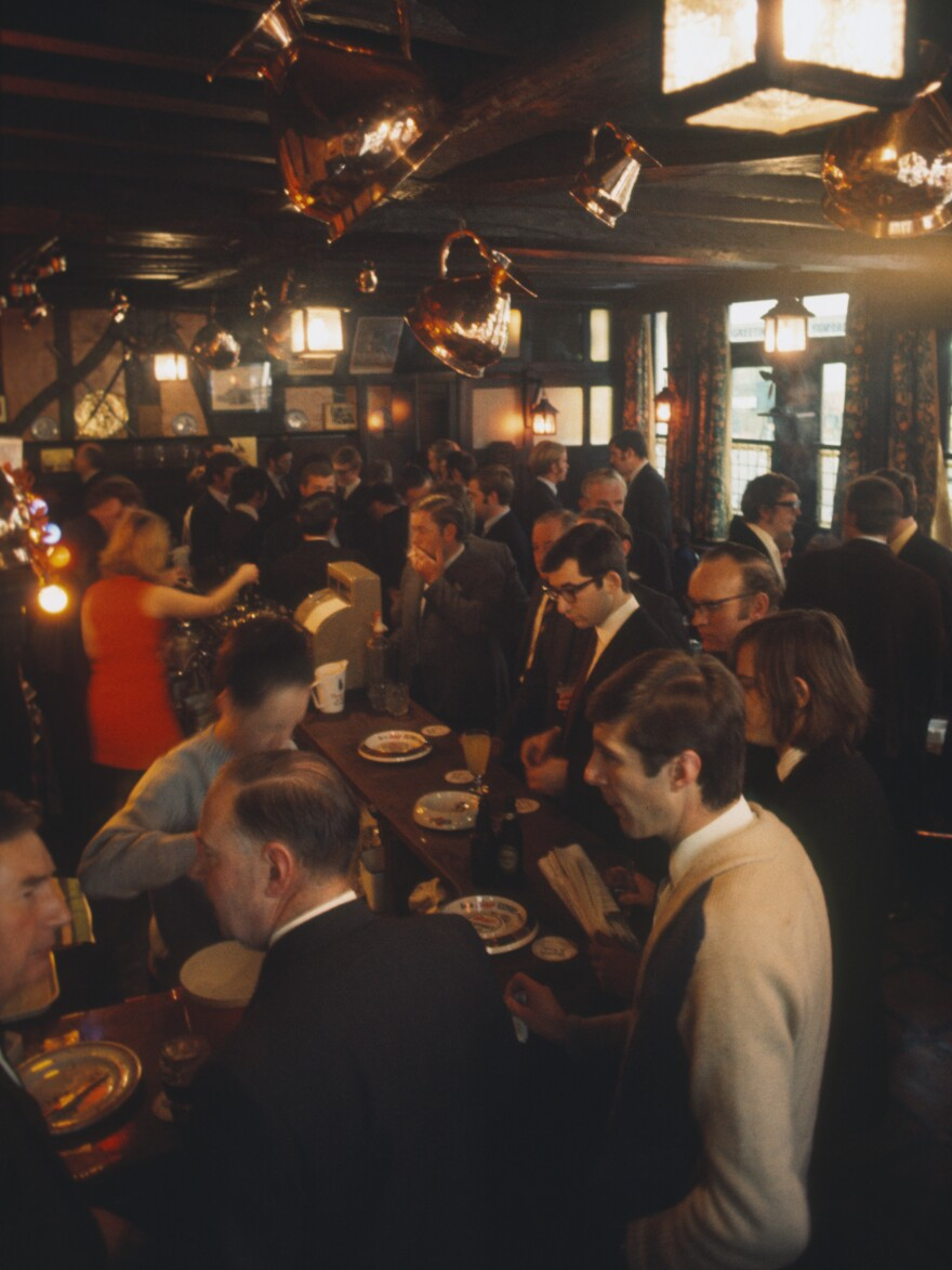 City workers meet and have a lunchtime pint at the bar in the Ye Olde Watling public house in London circa 1970.