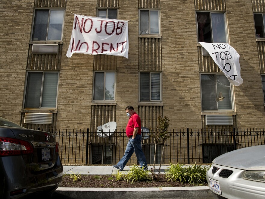 Signs hang from the windows of a Washington, D.C.,  apartment in May. Housing advocates and landlords say millions of out-of-work Americans won't be able to pay their rent if Congress doesn't extend or replace federal unemployment payments.