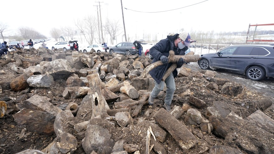 People collect firewood with others from a wood heap opened to the public on Wednesday in Dallas, as cold and snow have shut off power and left many homes around the state frigid.