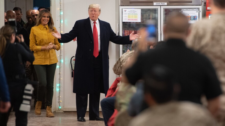 President Trump and first lady Melania Trump arrive to visit members of the U.S. military during an unannounced trip to Al Asad Air Base in Iraq on Wednesday. Reporters traveling with Trump, as has happened with past presidents, were not allowed to report that the president was in Iraq until the end of the visit for security purposes.