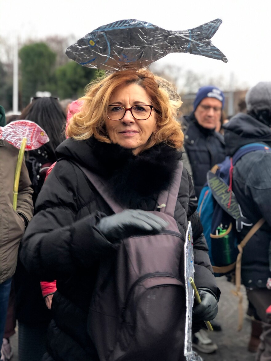 A participant at Sardines rally Bologna wearing a sardine on her head.