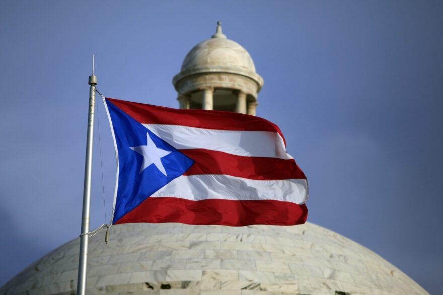 The Puerto Rican flag flies in front of Puerto Rico's Capitol as in San Juan, Puerto Rico, in July 2015 (Ricardo Arduengo/AP)