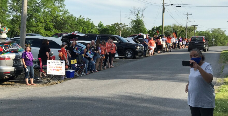 Teachers stand together up the street to cheer students as they drive by during Martinsburg High School's drive-through graduation on May 26, 2020.