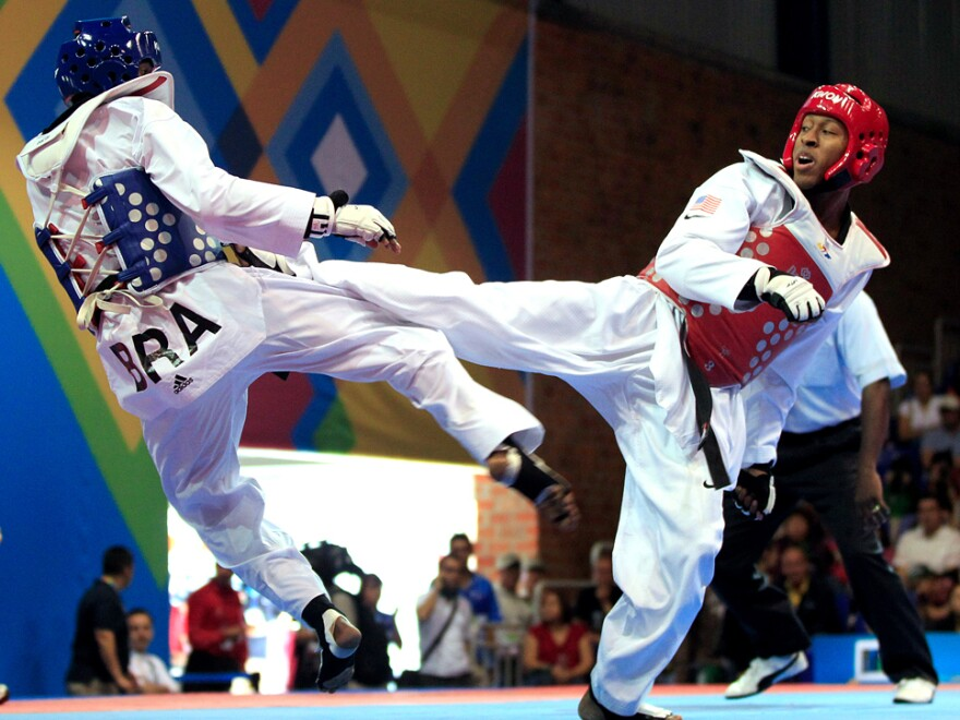 Terrence Jennings (right) lands a kick during a taekwondo match last fall. Jennings, who says his love of the <em>Teenage Mutant Ninja Turtles</em> drew him to the sport, will compete in his first Olympics this summer.