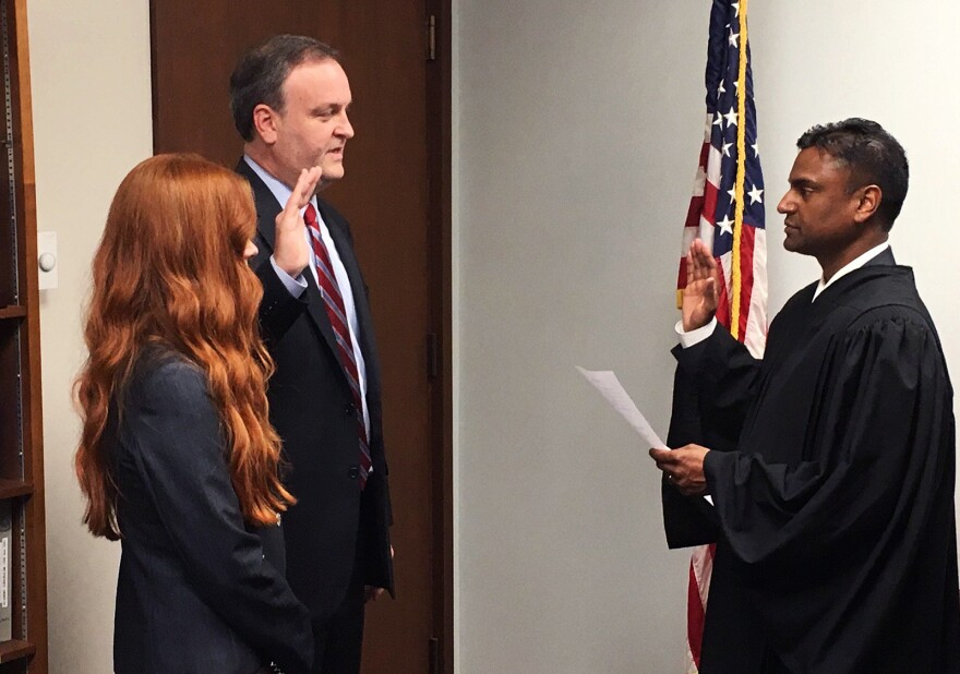 St. Louis County Councilman Sam Page (left), joined by his wife, Dr. Jennifer Page, is sworn in by Administrative Hearing Commissioner Sreenivasa Rao Dandamudi Monday to take over as county executive following Steve Stenger's resignation from the office.