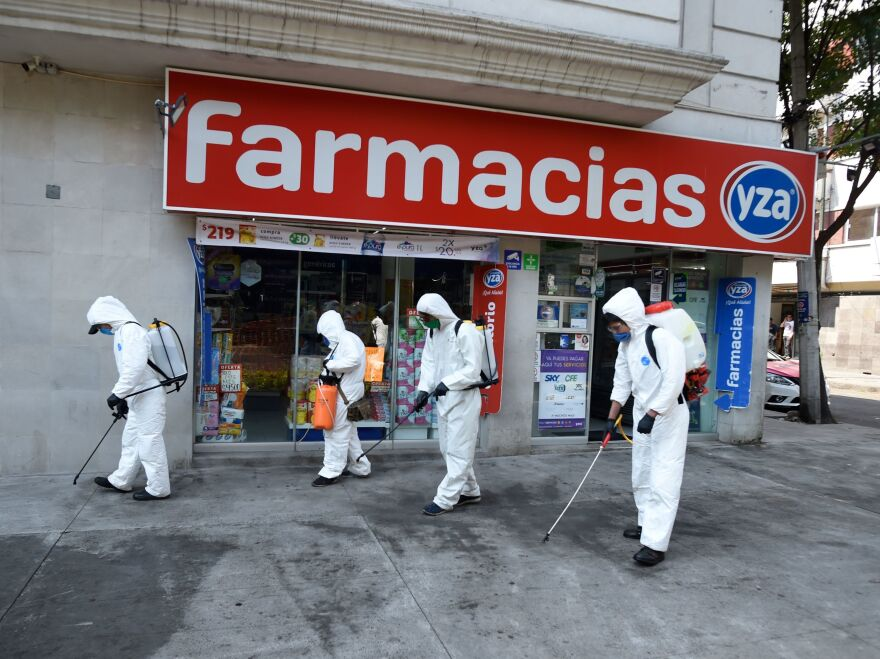 Cleaning workers wearing personal protective equipment disinfect a street in Mexico City amid the COVID-19 outbreak.