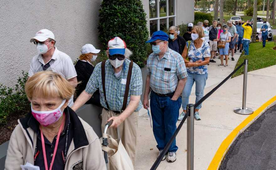 Seniors stand in line to make an appointment to receive the Moderna COVID-19 vaccine outside the King's Point clubhouse in Delray Beach, Florida on December 30, 2020.