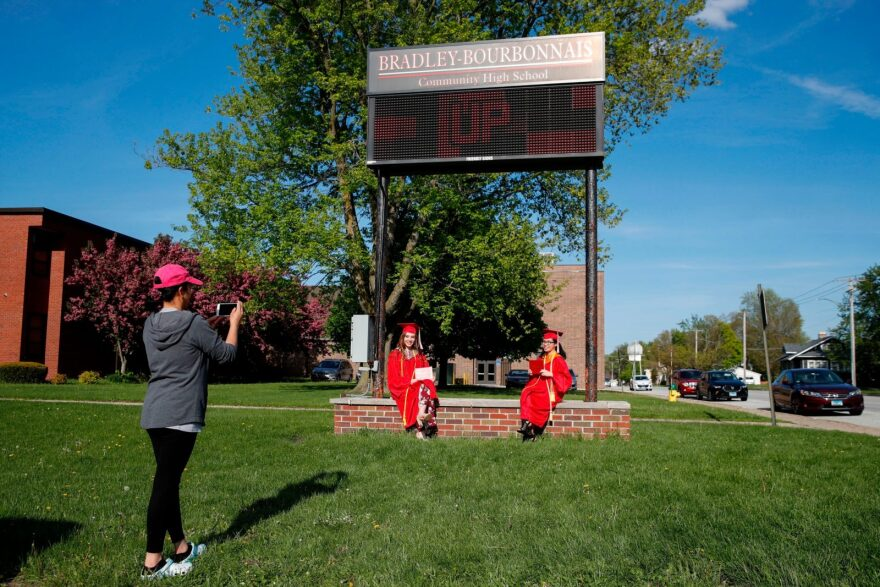 Students Maria Sosa (C) and Paulyn Bernadit (R) pose for a picture outside Bradley-Bourbonnais Community High School after picking up their diplomas during a graduation ceremony in Bradley, Illinois.