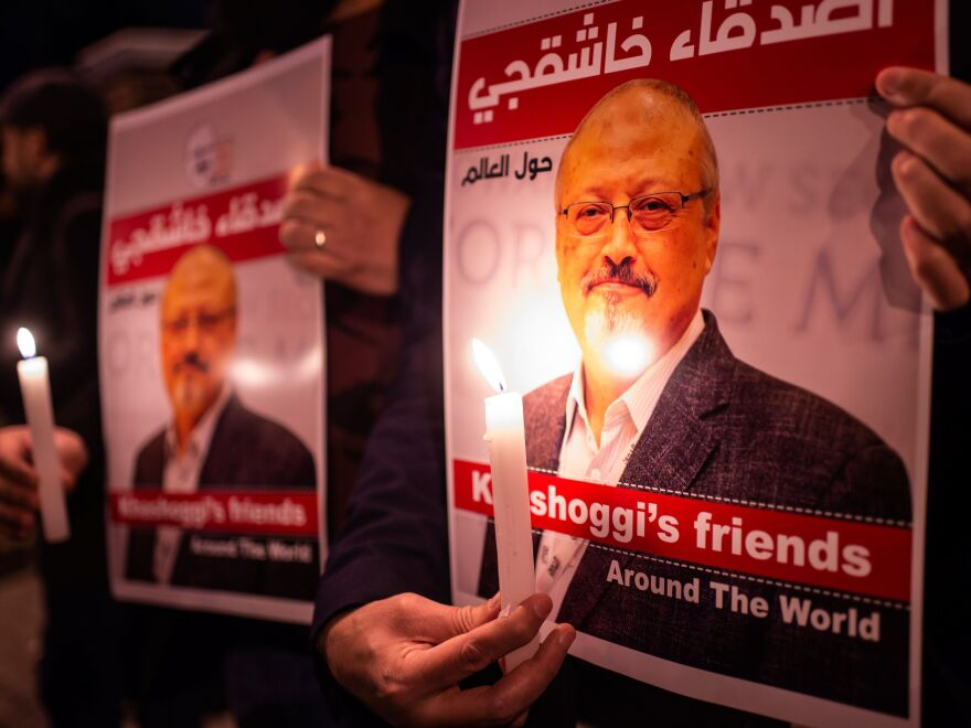 People hold posters picturing Saudi journalist Jamal Khashoggi and lit candles during a gathering outside Saudi Arabia's Consulate in Istanbul, on Oct. 25, 2018.