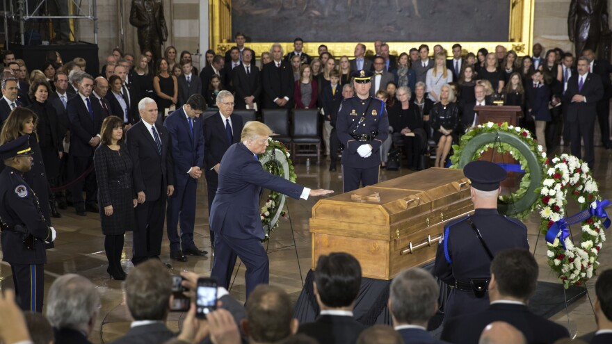President Trump touches the casket of the Rev. Billy Graham, who died last week at age 99, during a ceremony in the Capitol rotunda on Wednesday.