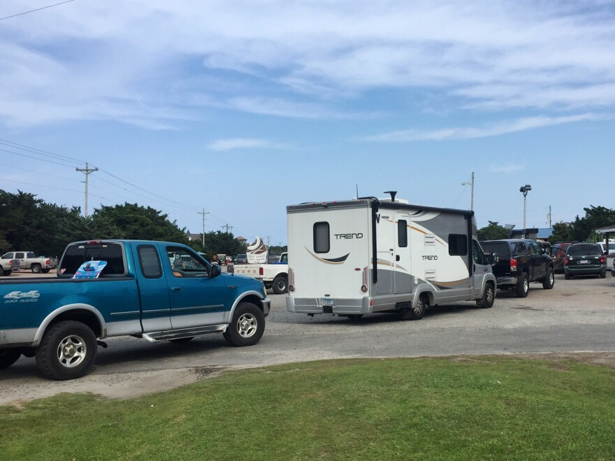 Vehicles line up Thursday at a gas station on Ocracoke Island of the Outer Banks. An estimated 10,000 tourists were ordered to evacuate the island after a construction company caused a power outage, leaving people stranded without air conditioning or places to eat.