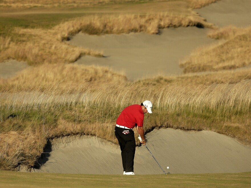 "Patrick Reed hits from the fairway on the 18th hole during the U.S. Open golf tournament at Chambers Bay. Some have criticized the grass's appearance, but others see it as ""the future of the game."""